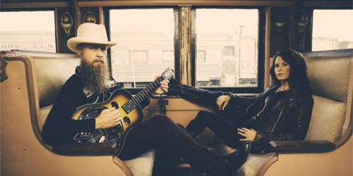 The Grahams - Man and woman sitting opposite each other on a train, Man is holding a guitar.